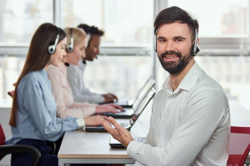 Καυκάσιος νεαρός άνδρας που δείχνει στους συναδέλφους του στο τηλεφωνικό κέντρο στοκ φωτογραφία με δικαίωμα ελεύθερης χρήσης