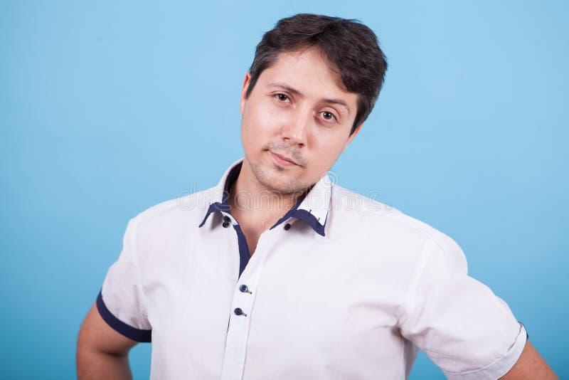 Καυκάσιος νεαρός άνδρας που κοιτά την κάμερα στο στούντιο με σηκωμένο φρύδι στοκ φωτογραφία με δικαίωμα ελεύθερης χρήσης