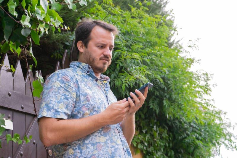 Καυκάσιος που κοιτάζει το έξυπνο τηλέφωνο με έκφραση θαυμασμού και σύγχυσης, διαβάζει ένα email Σοβαρός άνδρας που περιμένει, έλα στοκ φωτογραφία