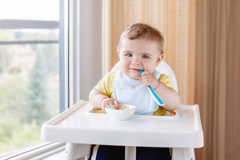 Καυκάσιο αγόρι παιδιών με τη βρώμικη ακατάστατη συνεδρίαση προσώπου στην υψηλή καρέκλα που τρώει τον πουρέ μήλων με το κουτάλι στοκ φωτογραφία με δικαίωμα ελεύθερης χρήσης