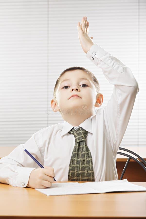 Καυκάσιο αγόρι που αυξάνει το χέρι στοκ εικόνες