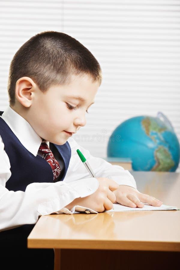 Καυκάσιο αγόρι που γράφει στο γραφείο sideview στοκ εικόνες