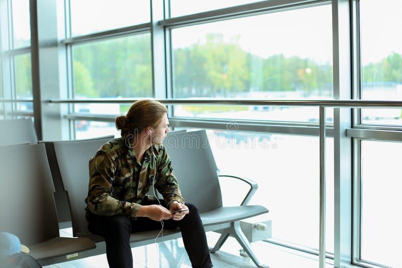 Καυκάσιο αγόρι που φορά το πουκάμισο κάλυψης, listenng στη μουσική και κάθισμα στη αίθουσα αναμονής στον αερολιμένα στοκ φωτογραφίες