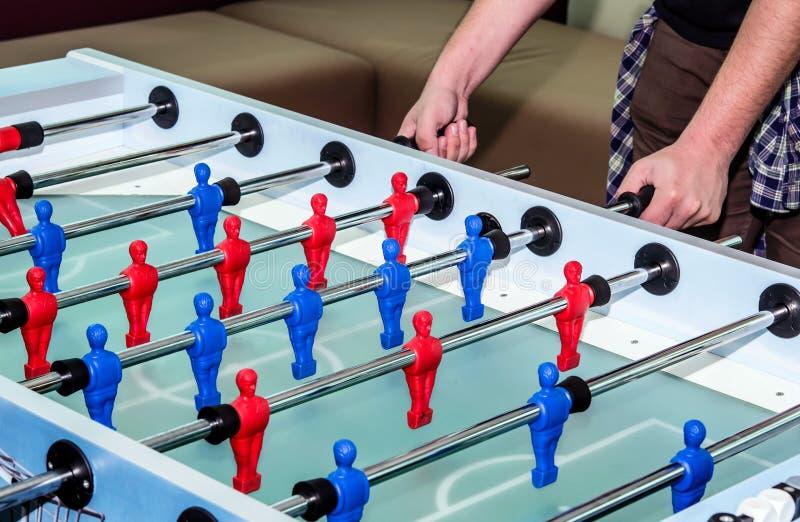 Καυκάσιο αρσενικό παίζοντας παιχνίδι επιτραπέζιου ποδοσφαίρου στοκ φωτογραφίες