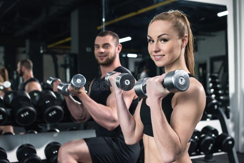 Καυκάσιο ζεύγος των αθλητών που εκπαιδεύουν με τους αλτήρες στη γυμναστική από κοινού στοκ φωτογραφία με δικαίωμα ελεύθερης χρήσης