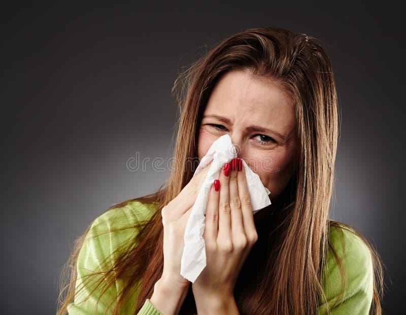 Καυκάσιο θηλυκό με τη γρίπη που φυσά τη μύτη της στοκ φωτογραφία