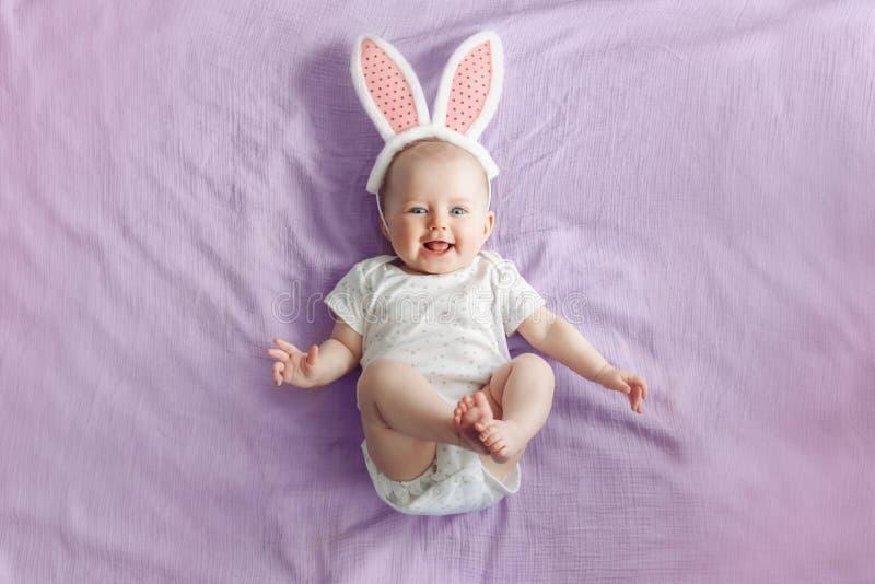 Καυκάσιο κοριτσάκι που φορά τα ρόδινα αυτιά λαγουδάκι Πάσχας που βρίσκονται στο ρόδινο πορφυρό κρεβάτι στην κρεβατοκάμαρα στοκ εικόνες