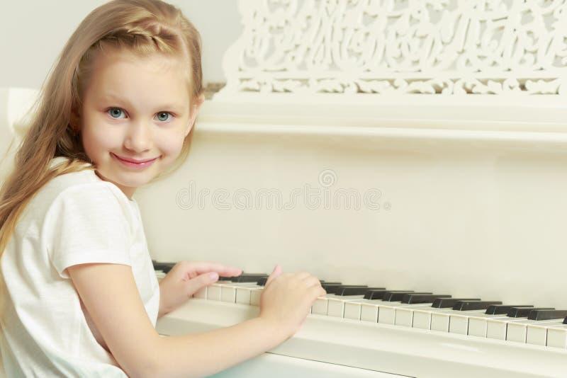 Καυκάσιο μικρό κορίτσι με τα μακριά ξανθά μαλλιά, σε ένα όμορφο ροζ στοκ εικόνα με δικαίωμα ελεύθερης χρήσης