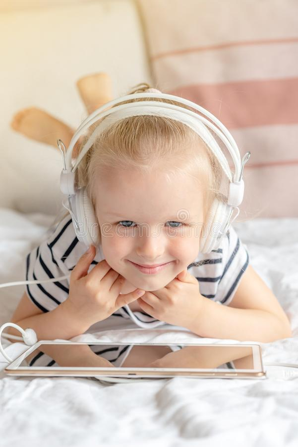 Καυκάσιο μικρό κορίτσι στην ταμπλέτα προσοχής ακουστικών στο κρεβάτι στοκ εικόνα με δικαίωμα ελεύθερης χρήσης
