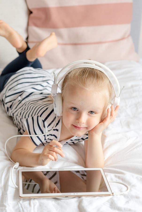 Καυκάσιο μικρό κορίτσι στην ταμπλέτα προσοχής ακουστικών στο κρεβάτι στοκ εικόνες με δικαίωμα ελεύθερης χρήσης