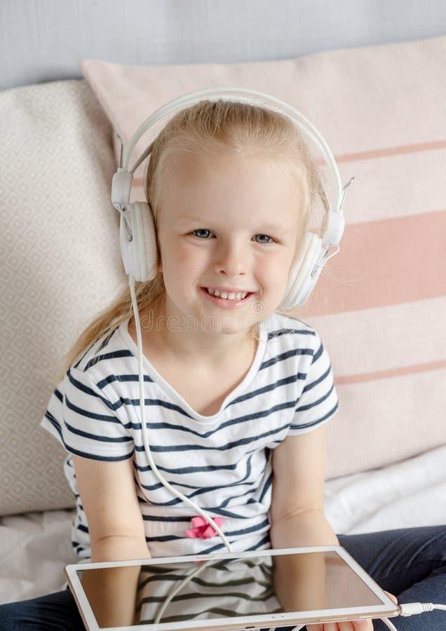 Καυκάσιο μικρό κορίτσι στην ταμπλέτα προσοχής ακουστικών στο κρεβάτι στοκ εικόνα