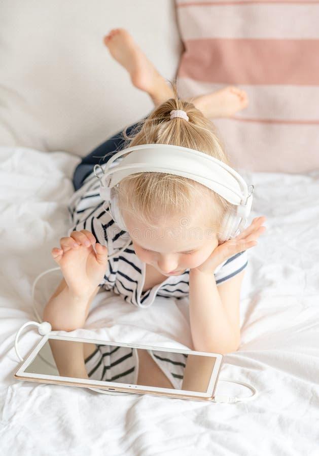 Καυκάσιο μικρό κορίτσι στην ταμπλέτα προσοχής ακουστικών στο κρεβάτι στοκ φωτογραφίες