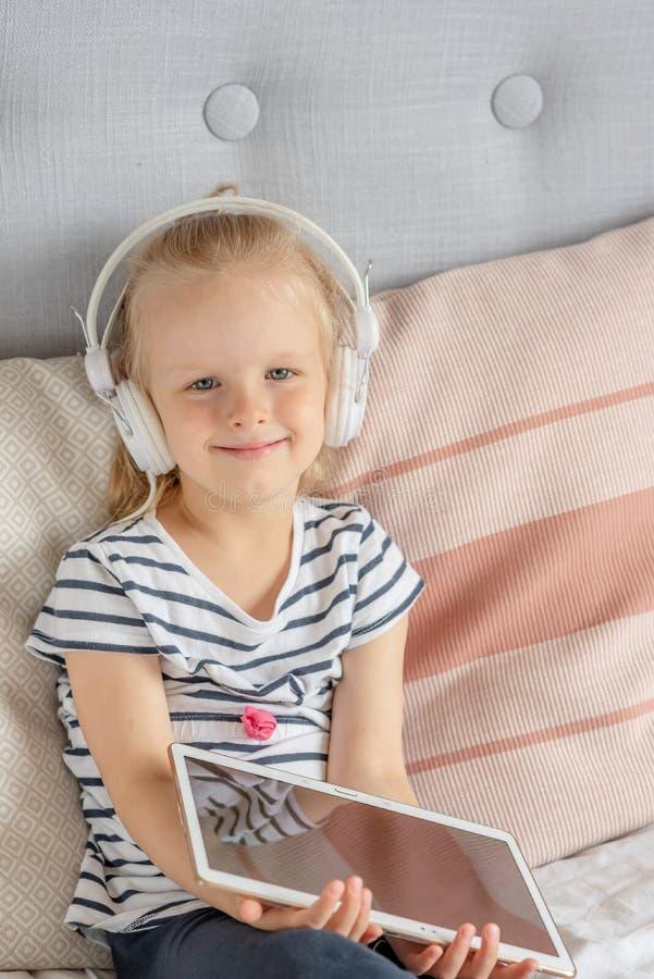 Καυκάσιο μικρό κορίτσι στην ταμπλέτα προσοχής ακουστικών στο κρεβάτι στοκ φωτογραφία