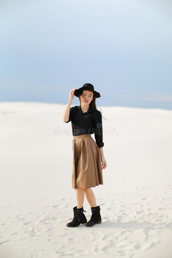 Καυκάσιο νέο κορίτσι που φορά τη φούστα, τη μαύρη μπλούζα με το καπέλο και τη στάση στο χιόνι στοκ φωτογραφία με δικαίωμα ελεύθερης χρήσης