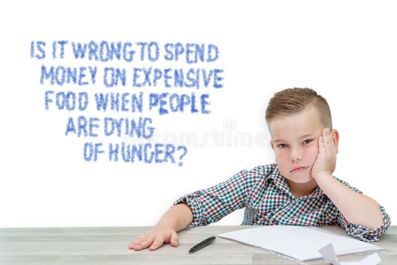 Καυκάσιο σχολικής ηλικίας αγόρι σε ένα πουκάμισο καρό που σκέφτεται για τα προβλήματα του κόσμου, για εάν για να αγοραστούν τα ακ στοκ εικόνες με δικαίωμα ελεύθερης χρήσης