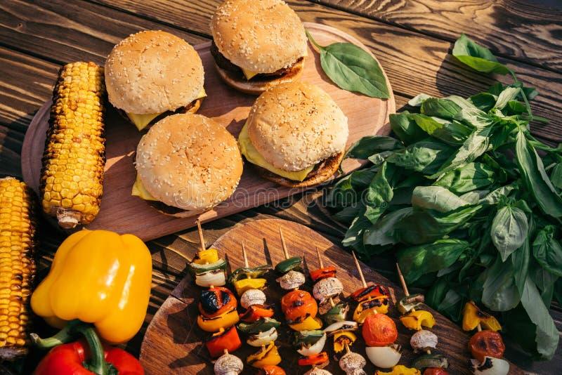 Καυτά εύγευστα burgers και λαχανικά που μαγειρεύονται υπαίθρια στη σχάρα στοκ εικόνες