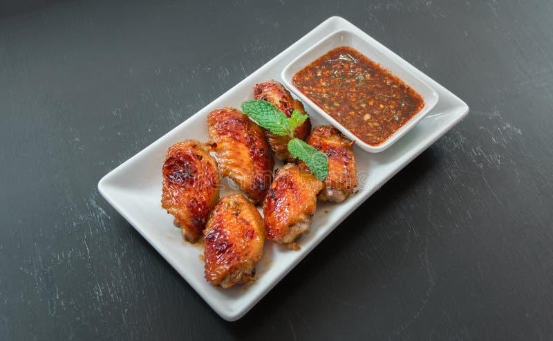 Καυτά πιάτα κρέατος - ψημένα στη σχάρα φτερά κοτόπουλου με το κόκκινο πικάντικο ταϊλανδικό styl στοκ φωτογραφία με δικαίωμα ελεύθερης χρήσης