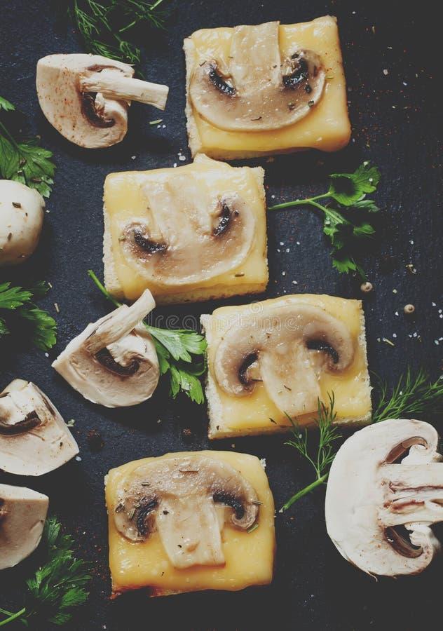 Καυτά σάντουιτς με το τυρί και τα μανιτάρια, πράσινα, σε ένα σκοτεινό ston στοκ εικόνα με δικαίωμα ελεύθερης χρήσης