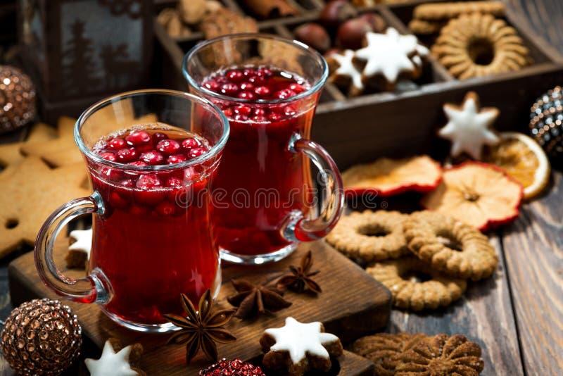 Καυτά τσάι και μπισκότα των βακκίνιων Χριστουγέννων στο σκοτεινό πίνακα στοκ εικόνες