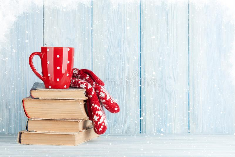 Καυτά φλυτζάνι και γάντια σοκολάτας πέρα από τα βιβλία στοκ εικόνα