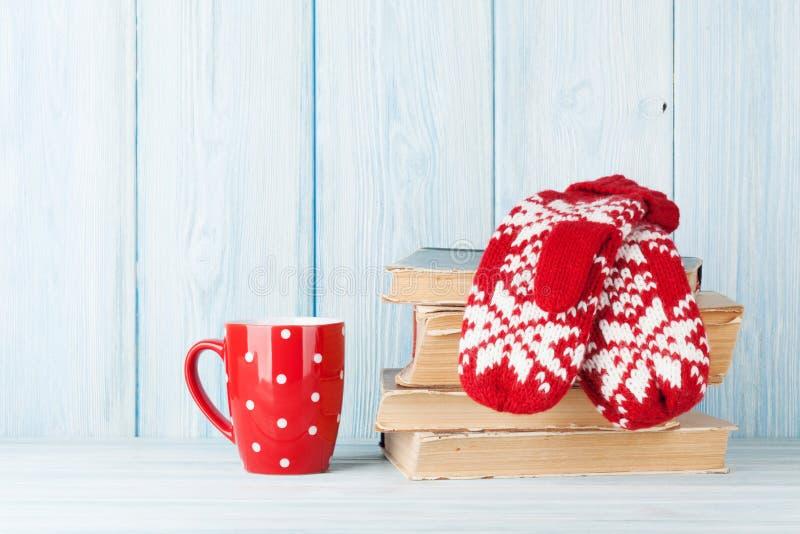 Καυτά φλυτζάνι και γάντια σοκολάτας πέρα από τα βιβλία στοκ φωτογραφία