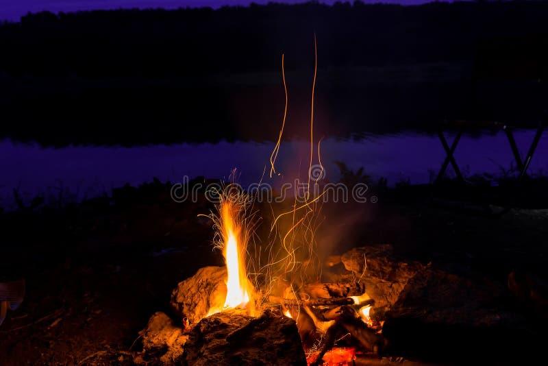 Καυτές φλόγες πυρκαγιάς στο σκοτάδι μεγαλοπρεπής πυρκαγιά με τους σπινθήρες τη νύχτα στοκ φωτογραφία
