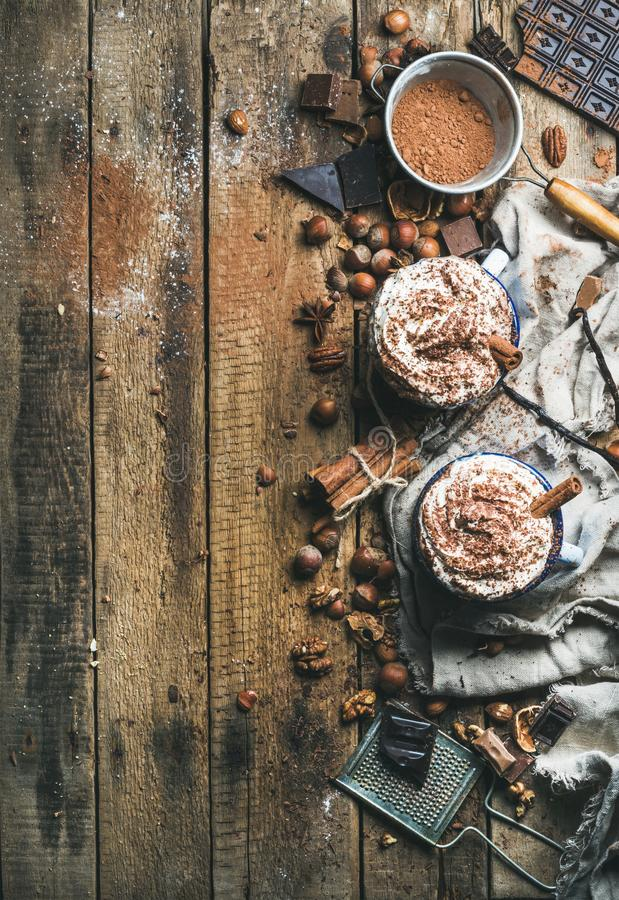 Καυτή σοκολάτα με την κτυπημένα κρέμα, τα καρύδια, τα καρυκεύματα και τη σκόνη κακάου στοκ φωτογραφίες