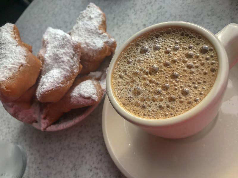 Καυτοί καφές και Beignets ραδικιού στοκ φωτογραφία