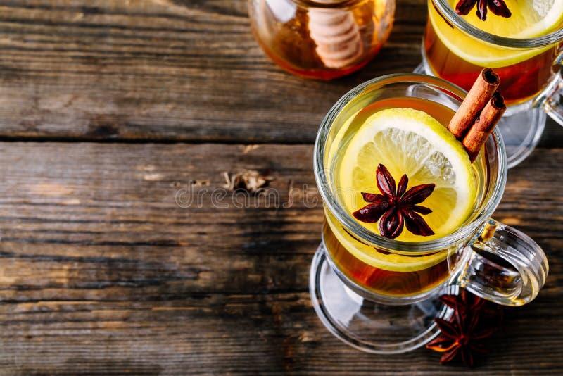 Καυτός καρυκευμένος χυμός φοινικόδεντρου μηλίτη της Apple με το ραβδί λεμονιών, μελιού και κανέλας στο γυαλί στοκ φωτογραφία