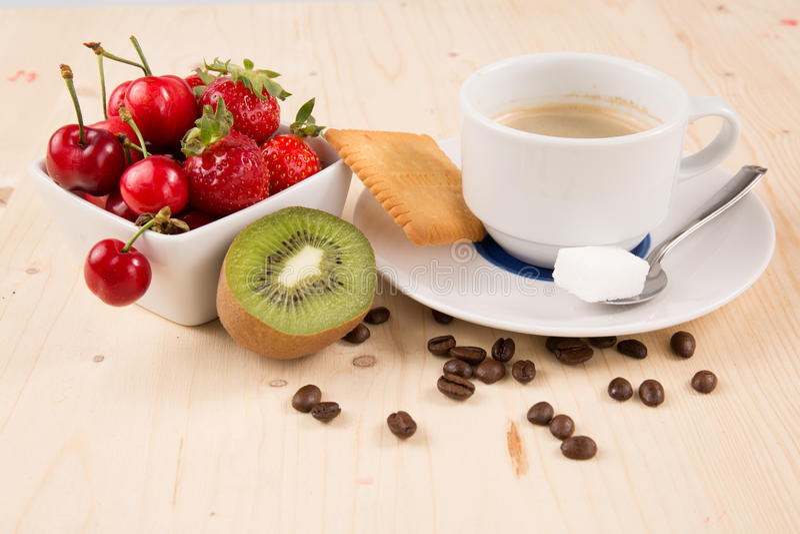 Καυτός καφές, κέικ, κεράσι, φράουλα, στον ξύλινο πίνακα στοκ φωτογραφία
