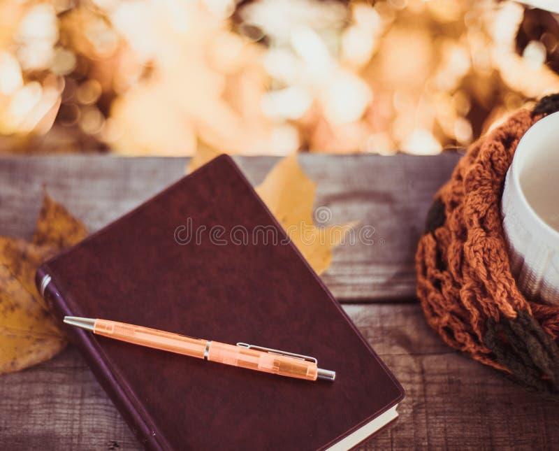 Καυτός καφές και κόκκινο βιβλίο με τα φύλλα φθινοπώρου στο ξύλινο υπόβαθρο - εποχιακό χαλαρώστε την έννοια στοκ εικόνα