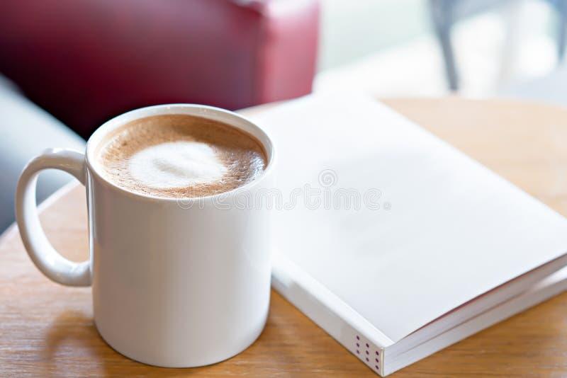 Καυτός καφές με το βιβλίο στον πίνακα Πάρτε μια έννοια σπασιμάτων στοκ φωτογραφίες