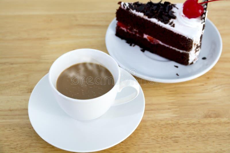 Καυτός καφές σε ένα άσπρο φλυτζάνι και ένα μουτζουρωμένο μαύρο κέικ σοκολάτας στοκ εικόνα