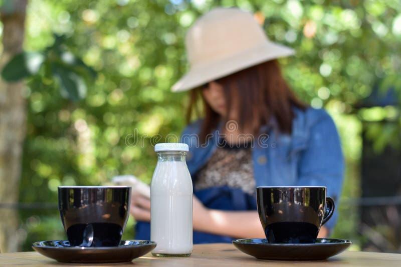 Καυτός καφές σε ένα μαύρο φλυτζάνι και γάλα σε έναν ξύλινο πίνακα με το θολωμένο υπόβαθρο προσώπων στοκ εικόνες με δικαίωμα ελεύθερης χρήσης