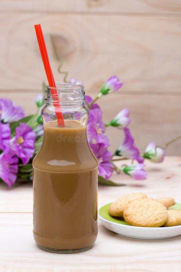 Καυτός καφές στο μπουκάλι και βουτύρου μπισκότο στο ξύλο στοκ εικόνες
