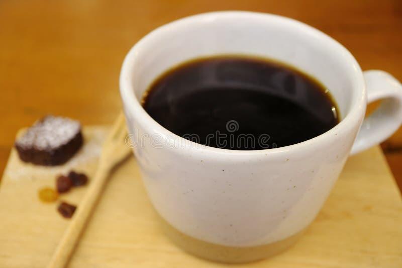 Καυτός μαύρος καφές σε ένα άσπρο φλυτζάνι στον ξύλινο δίσκο, εκλεκτική εστίαση στοκ εικόνες με δικαίωμα ελεύθερης χρήσης
