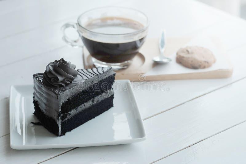 Καυτός μαύρος καφές americano και κομμάτι Α του κέικ ξυλάνθρακα στον άσπρο ξύλινο πίνακα στοκ εικόνες