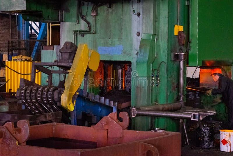 Καυτός σίδηρος στο smeltery που κατέχει ένας εργαζόμενος Καυτό προϊόν σφυρηλατημένων κομματιών υψηλής ακρίβειας, αυτοκίνητη παραγ στοκ φωτογραφία με δικαίωμα ελεύθερης χρήσης