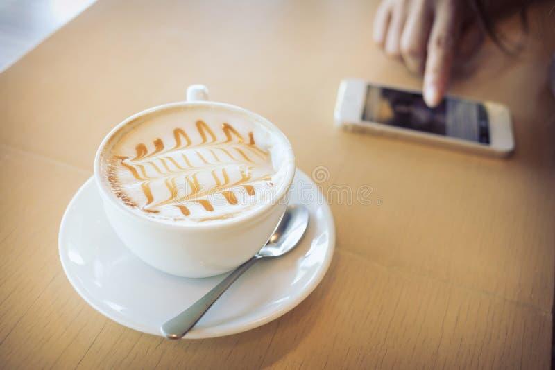Καυτός του ποτού καφέ στον ξύλινο επιτραπέζιο φραγμό με το κινητό τηλέφωνο στοκ φωτογραφίες