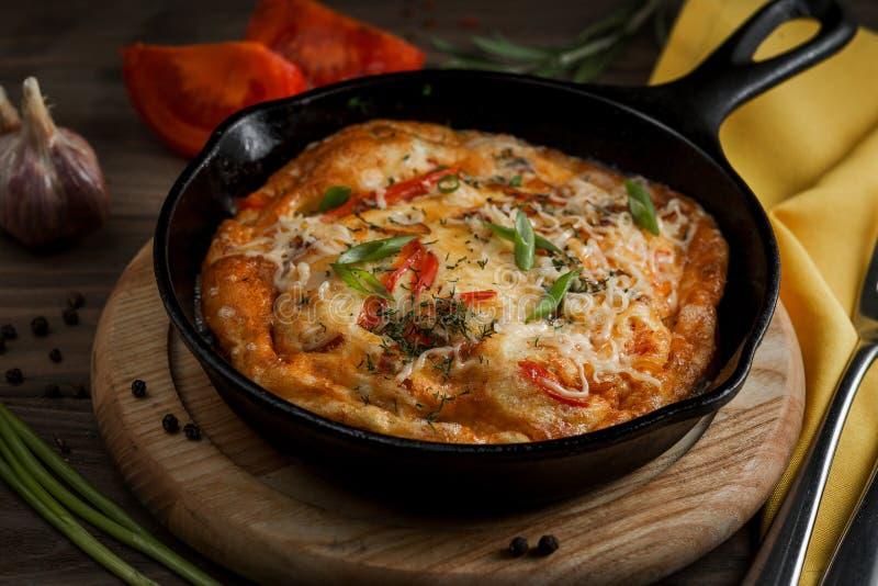 Καυτό τηγάνι με την ομελέτα και λαχανικά σε έναν ξύλινο πίνακα στοκ εικόνα