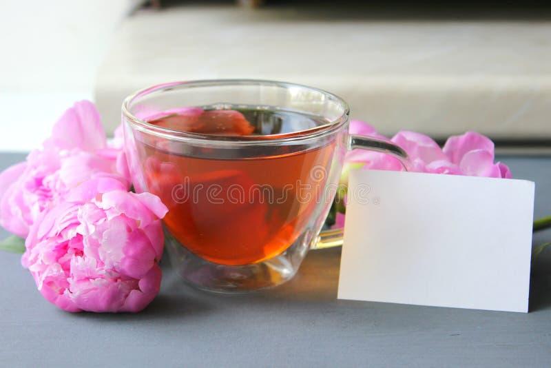Καυτό τσάι σε ένα διαφανές φλυτζάνι, μια ανθοδέσμη των ρόδινων peonies σε ένα σκοτεινό υπόβαθρο στοκ φωτογραφία με δικαίωμα ελεύθερης χρήσης