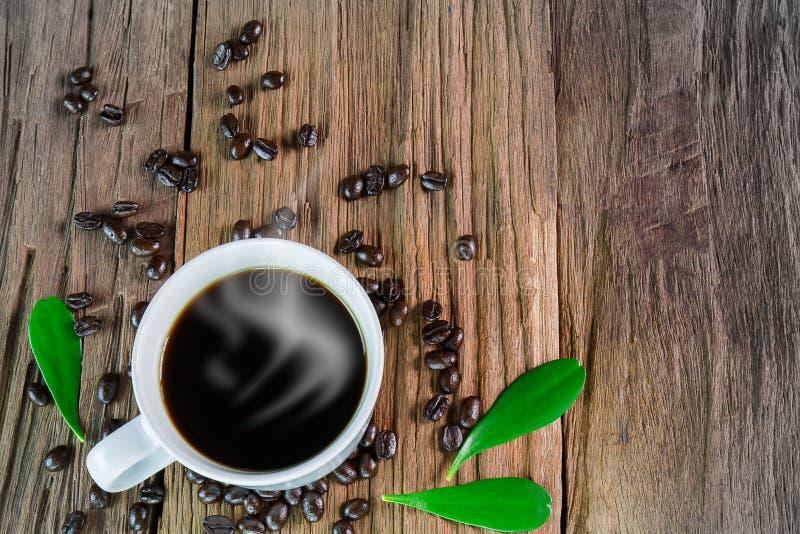 Καυτό φλιτζάνι του καφέ με τον καπνό, τα φασόλια καφέ και τα φύλλα στο εκλεκτής ποιότητας ξύλινο υπόβαθρο grunge στοκ φωτογραφίες