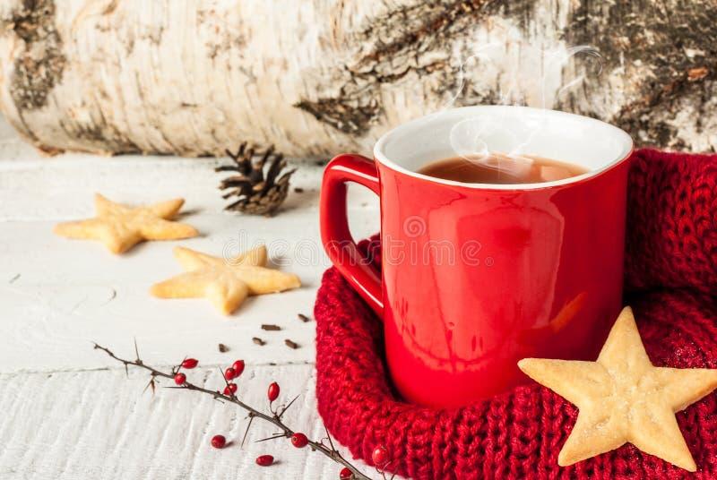 Καυτό χειμερινό τσάι σε μια κόκκινη κούπα με τα μπισκότα Χριστουγέννων στοκ φωτογραφία με δικαίωμα ελεύθερης χρήσης