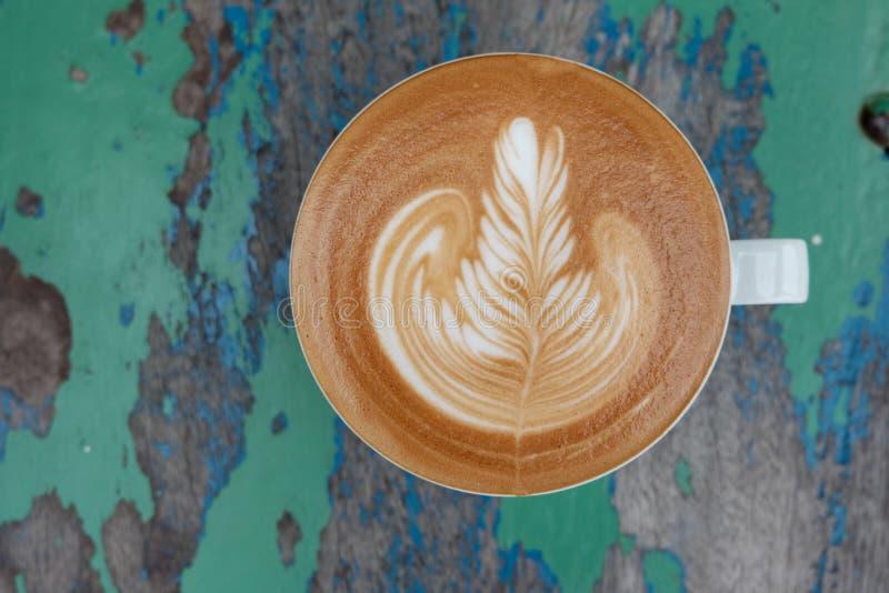 Καυτό latte εστίασης του φλυτζανιού στο ξύλο στοκ φωτογραφία