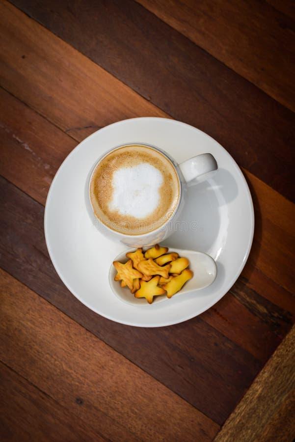 Καυτό latte φλιτζανιών του καφέ στον ξύλινο πίνακα στοκ εικόνα με δικαίωμα ελεύθερης χρήσης