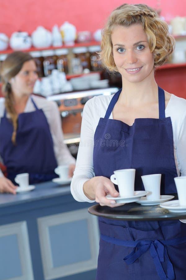 Καφέδες δίσκων εκμετάλλευσης σερβιτορών πορτρέτου στοκ εικόνα