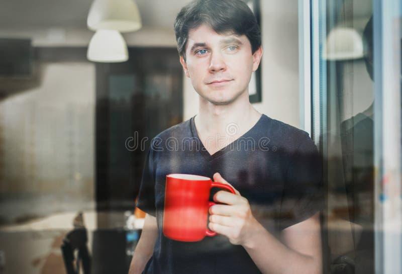 Καφές ή τσάι κατανάλωσης ατόμων κοντά στο παράθυρο στοκ φωτογραφία