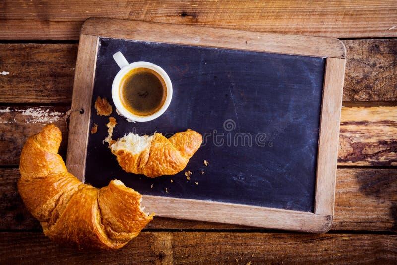 Καφές και ένας croissant σε μια πλάκα παλιών σχολείων στοκ εικόνες με δικαίωμα ελεύθερης χρήσης