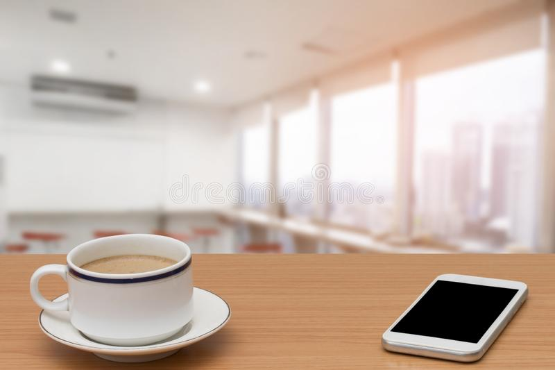 Καφές και smartphone στον ξύλινο πίνακα με θολωμένος του σύγχρονου εσωτερικού κουζινών για το υπόβαθρο στοκ φωτογραφίες με δικαίωμα ελεύθερης χρήσης