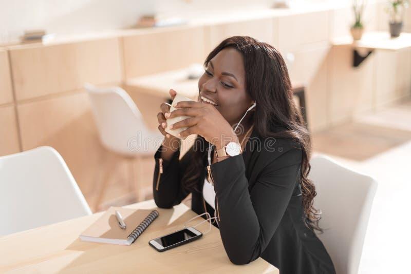 Καφές κατανάλωσης γυναικών αφροαμερικάνων και μουσική ακούσματος με τα ακουστικά στον καφέ στοκ φωτογραφίες με δικαίωμα ελεύθερης χρήσης
